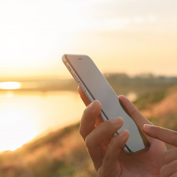 closeup hand using phone outdoor at sunset